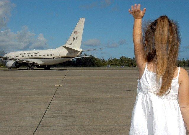 飛行機に向かって手を振る子ども