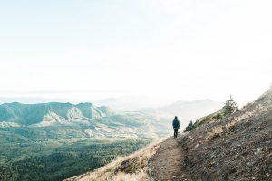 標高の高い山の上の登山道を一人で歩く人の後ろ姿