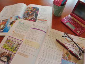 机の上に広げられた電子辞書とメガネと参考書