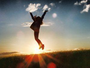 喜んで夕日に照らされながらジャンプしている人