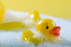 浴槽の泡の上に浮かんだアヒルのおもちゃ