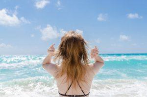 海辺で髪をかき上げる金髪女性の後ろ姿