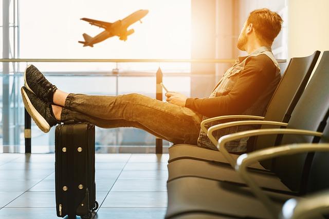 飛び立つ飛行機を眺めて椅子に座っている男性