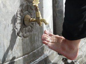 水道で足を洗う人の左足