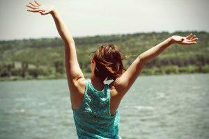 湖を前に背伸びする女性の後ろ姿