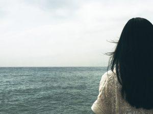 海を眺める黒髪女性の後ろ姿