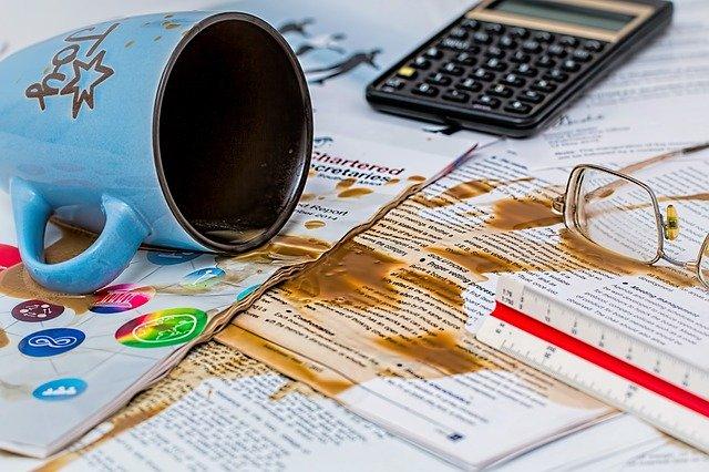 英文書類の上にこぼれたコーヒー