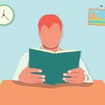 机に座って本を読む赤毛の男性