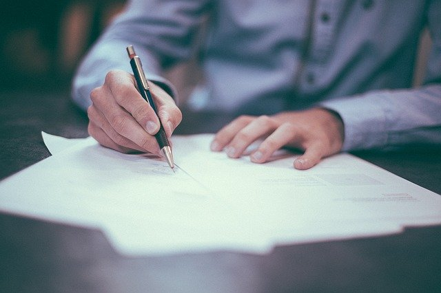 書類に文字を書き込む男性の手