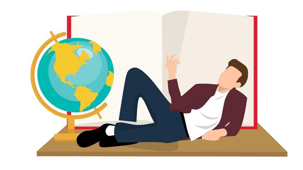 開かれた本の前の地球儀と横たわってくつろぐ男性