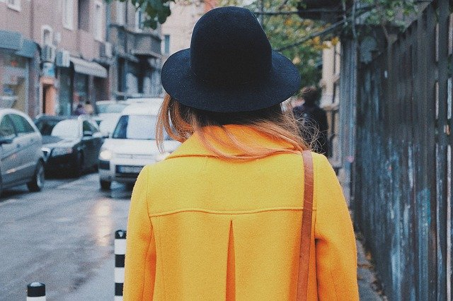 黄色いコートを着た女性の後ろ姿